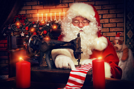 Santa Claus is sewing on a sewing machine striped socks for Christmas. photo
