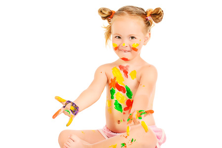 Joyful little girl covered in paint. Art and painting concept. Happy childhood. Education. Isolated over white background. photo