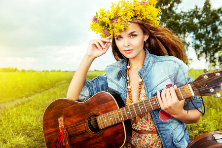 Romantic girl in a wreath of wild flowers playing her guitar. Summer. Hippie style.  photo