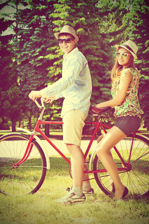 Happy young couple in summer park rides a bike. Romance and love. photo