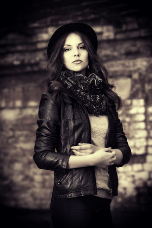 Black-and-white portrait of a beautiful young woman in leather jacket posing over brick wall. photo