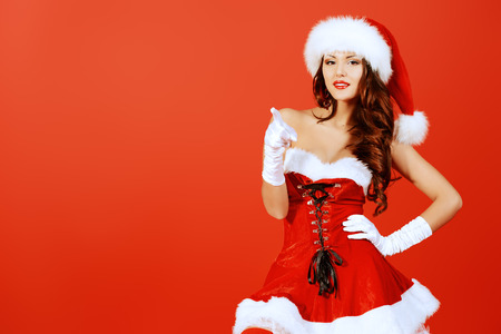 Attractive young woman in Santa Claus costume over red background. Christmas. photo