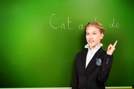 schoolgirl uniform: Smiling schoolgirl performs the task at the blackboard. Education. Stock Photo