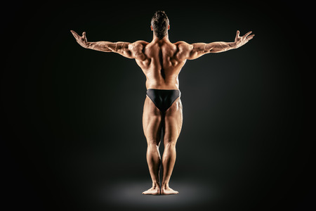 dorsi: Beautiful muscular man bodybuilder posing back over dark background. Full length. Stock Photo