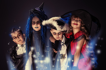 kid smiling: Cheerful children in halloween costumes posing over dark background. Stock Photo