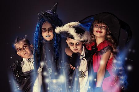 mago: Niños alegres en disfraces de halloween posando sobre fondo oscuro.