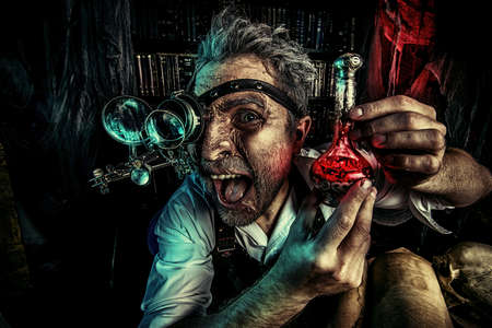 inventor: Portrait of a crazy medieval scientist working in his laboratory. Alchemist. Halloween. Stock Photo