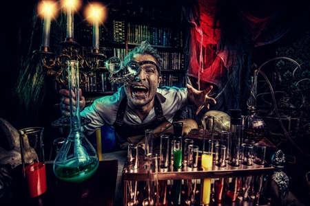 crazy man: Portrait of a crazy medieval scientist working in his laboratory. Alchemist. Halloween. Stock Photo