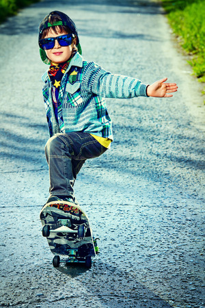 Cool 7 year old boy with his skateboard on the street.\ Childhood. Summertime.