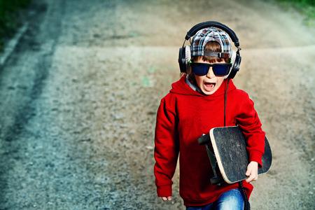 ni�o en patines: Enfriar ni�o de 7 a�os con su patineta en la calle. Infancia. Summertime. Foto de archivo