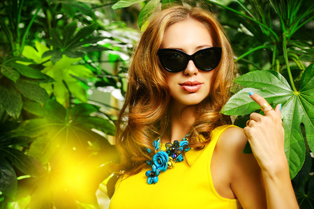 Attractive young woman  among the tropical plants. Vacation. Tropics. Fashion shot. photo