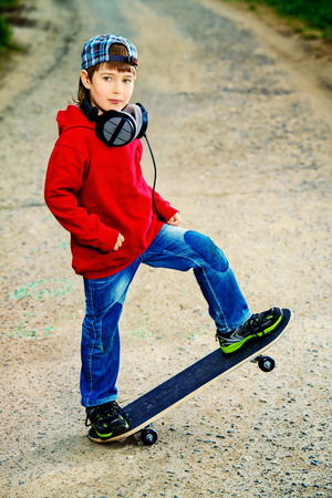 cool boys: Modern boy with his skateboard on the street. Childhood. Summertime.