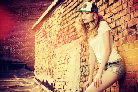 caps: Beautiful modern girl near the brickwall in the rays of the evening sun. Youth style. Fashion shot. Stock Photo