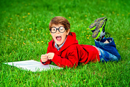 Cute 7 years old boy lying on a grass with a book and shouting. photo