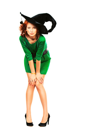 Charming red-haired witch. Halloween. Isolated over white.  photo
