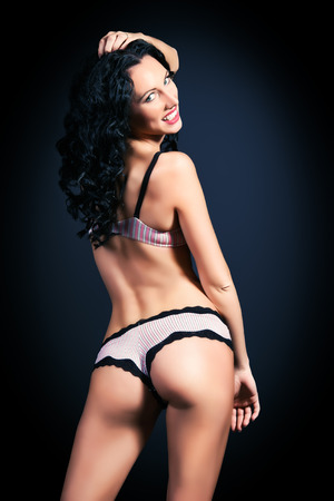 black women naked: Sexual young woman in beautiful lingerie standing back. Black background.
