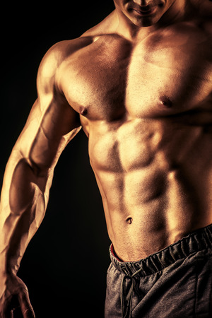 Close-up shot of a handsome muscular bodybuilder posing over black background. photo