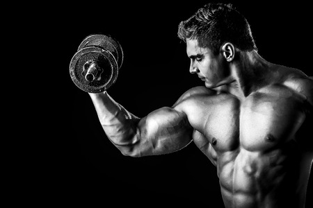 Portrait of a handsome muscular bodybuilder posing with dumbbells over black background. photo