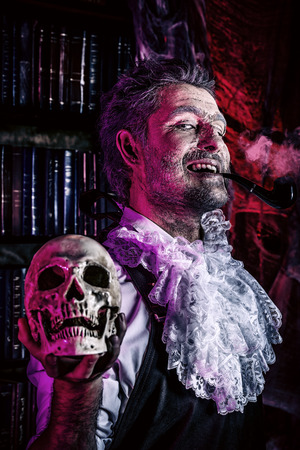 scary man: Close-up portrait of an old medieval scientist holding a skull. Alchemist. Halloween. Stock Photo