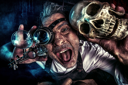 secret society: Close-up portrait of an old medieval scientist holding a skull. Alchemist. Halloween. Stock Photo