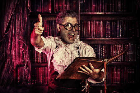 scary man: Crazy medieval scientist working in his laboratory with old manuscripts. Alchemist. Halloween. Stock Photo
