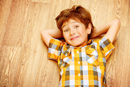 linoleum: Happy smiling boy lying on a floor at home. Happy childhood.