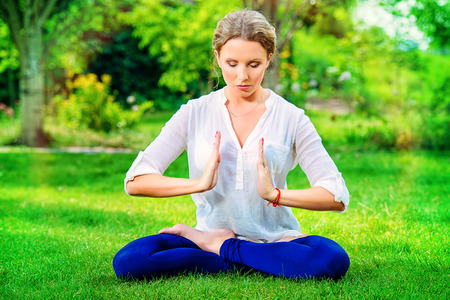 Beautiful young woman doing yoga in the summer park. Healthy lifestyle. Yoga. photo