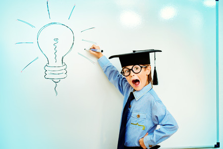 Smart boy stands by the whiteboard in a classroom expressing new idea. Educational concept. Copy space. photo