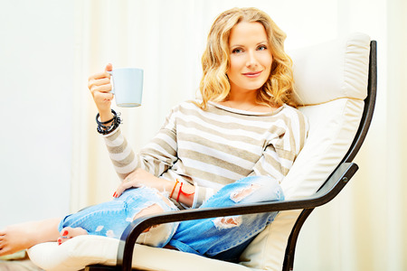 cosiness: Beautiful young woman resting at home in a cozy armchair with a cup of tea. Interior. Stock Photo