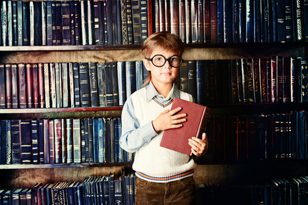 Smart boy stands in the library by the bookshelves with many old books. Educational concept. Science. photo