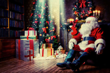 Kerstman bracht geschenken voor kerst en met een rust bij de open haard. Woondecoratie.
