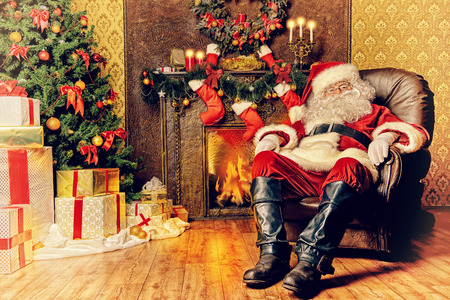 traditional gifts: Santa Claus brought gifts for Christmas and having a rest by the fireplace. Home decoration.