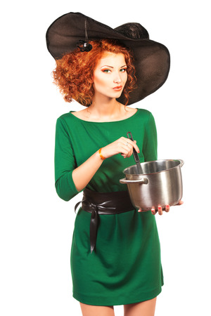 brew: Charming red-haired witch brews a witchs brew. Halloween. Isolated over white.