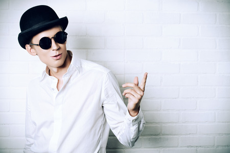 fop: Fashion shot of a modern young man in white shirt, black bowler hat and round sunglasses.  Stock Photo