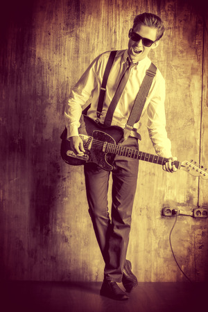 31647318: Expressive young man playing rock-n-roll music on his electric guitar. Retro, vintage style.