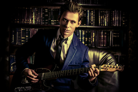 Handsome young man playing rock-n-roll music on his electric guitar. Retro, vintage style.  photo