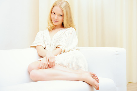 Pretty young woman sitting on a sofa at home and smiles. Interior. photo