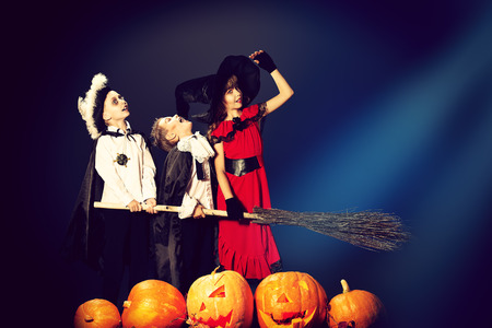 Cheerful children in halloween costumes standing with pumpkins and a broom. Over dark background. photo
