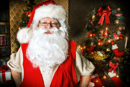 Santa Claus standing at home with gifts, dressed in his home clothes. Christmas. Decoration. photo