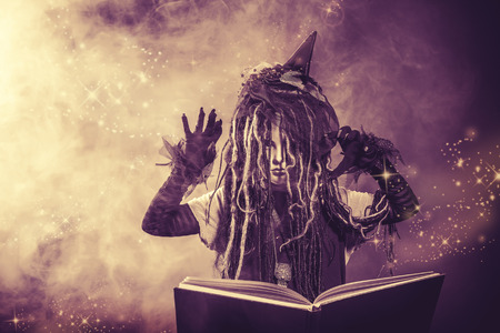 spell: Little girl in a costume of witch casts a spell over magic book. Black-and-white photo.