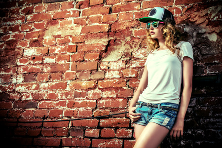 urban style: Beautiful modern girl near the brickwall. Youth style. Fashion shot. Stock Photo