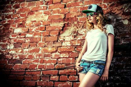 juventud: Chica moderna hermosa cerca de la brickwall. Estilo de la Juventud. Disparo de moda.