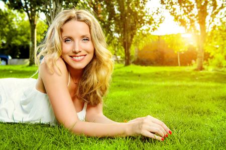 attraktiv: Close-up-Porträt einer schönen lächelnden Frau auf einem Gras im Freien liegen. Sie ist absolut glücklich.