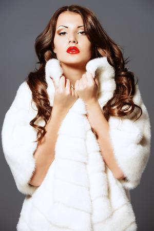 white fur: Moda foto de una hermosa mujer joven en abrigo de piel blanco. Foto de archivo