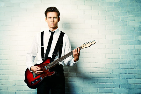 pop singer: Expressive young man playing rock-n-roll music on his electric guitar. Retro, vintage style.