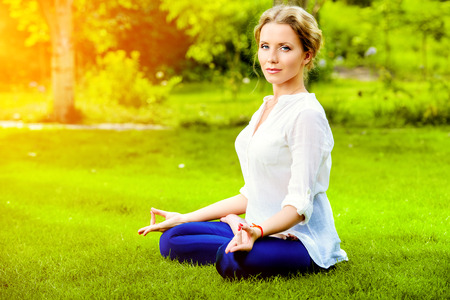 Beautiful young woman doing yoga in the summer park. Healthy lifestyle. Yoga. Lotus pose. photo