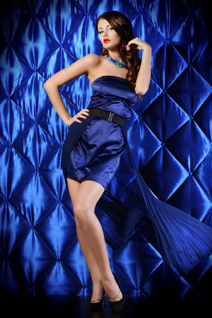 Seductive young woman in  beautiful dress over vintage background.