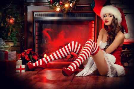 stocking cap: Sexual young woman in Santa Claus costume posing in Christmas decorations.