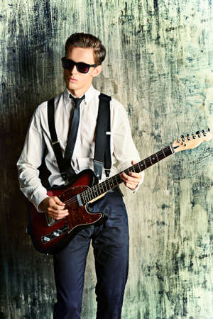 31798241: Expressive young man playing rock-n-roll music on his electric guitar. Retro, vintage style.