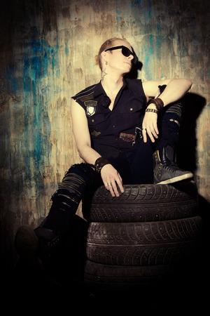 Masculine handsome man in the old garage. Rock singer. Grunge style. photo